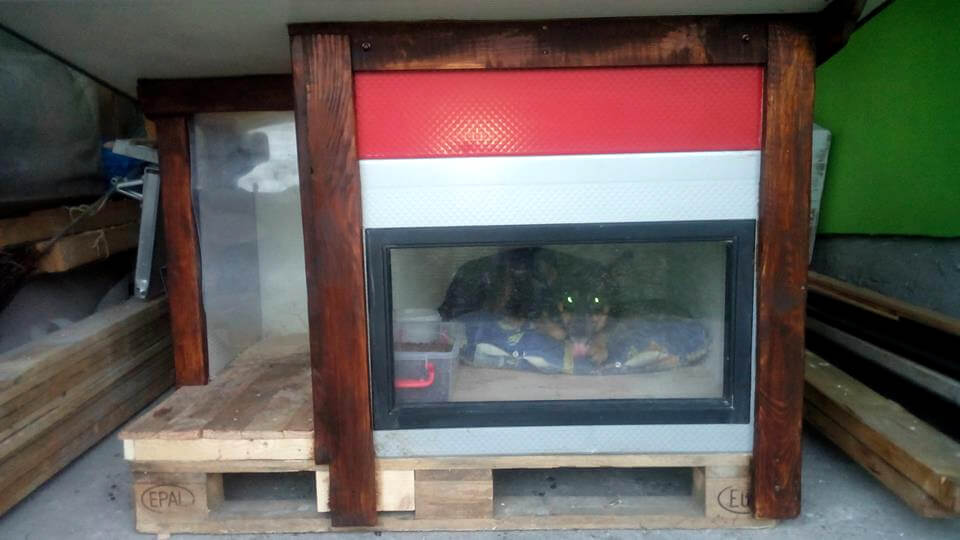 repurposed pallet and old door panels dog house